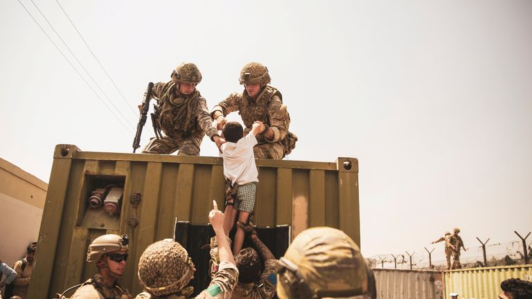 UK coalition forces, Turkish coalition forces, and U.S. Marines assist a child during an evacuation at Hamid Karzai International Airport, Kabul, Afghanistan, in this photo taken on August 20, 2021.  Sgt. Victor Mancilla/U.S. Marine Corps/Handoutvia REUTERS THIS IMAGE HAS BEEN SUPPLIED BY A THIRD PARTY.     TPX IMAGES OF THE DAY