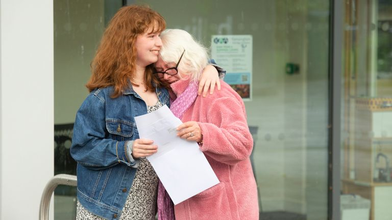 An emotional student hugs her mother at a school in London
