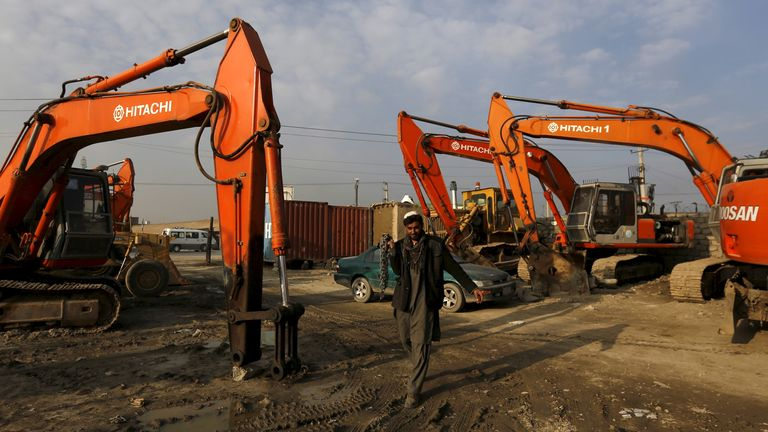 A man walks next to machinery parked at the Omid Gardizi construction company in Kabul, Afghanistan November 30, 2015.