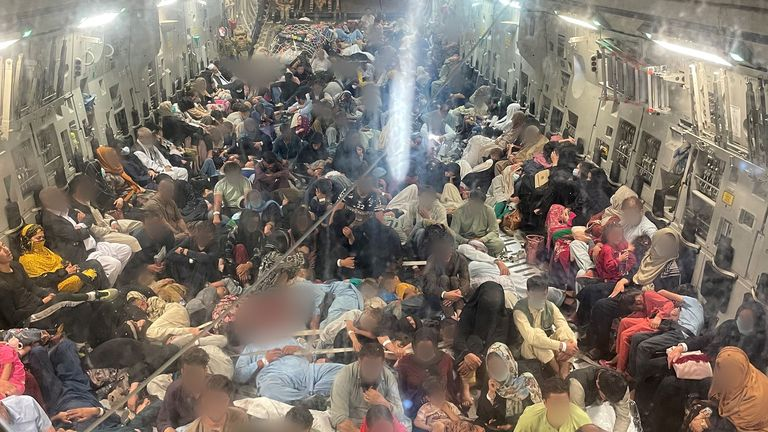 Passengers sit inside a Royal Air Force C-17 following evacuation from Kabul airport