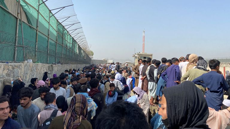 Crowds of people gather near the airport in Kabul