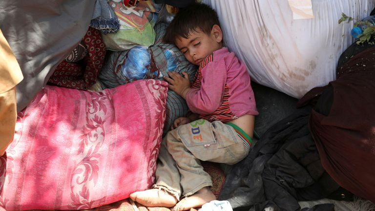 An internally displaced child from northern provinces sleeps in a park  in Kabul