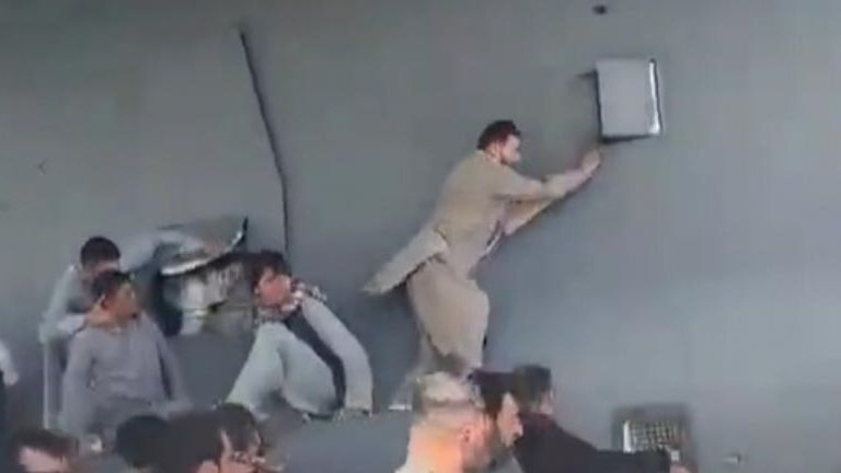 AFGHAN LOCALS CLING TO PLANE