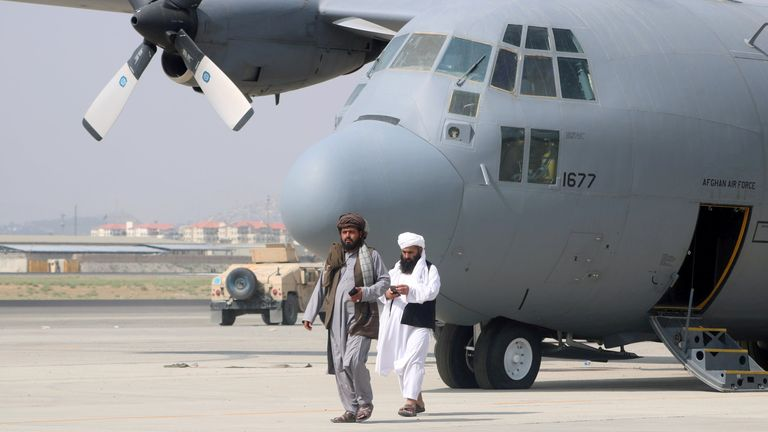 Taliban walk in front of a military airplane a day after the U.S. troops withdrawal from Hamid Karzai International Airport in Kabul, Afghanistan
