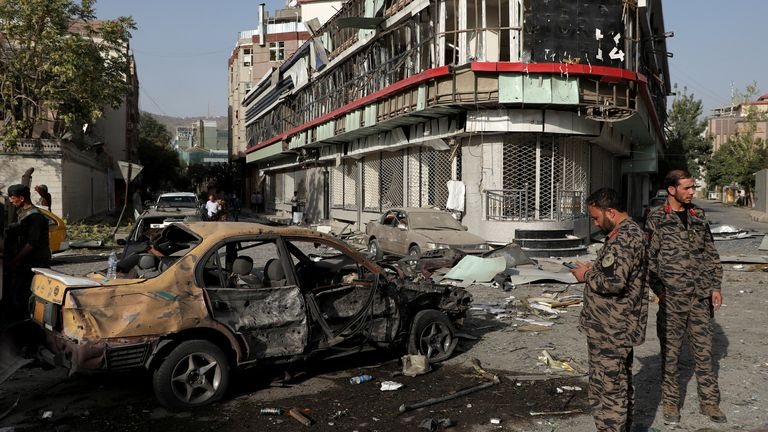 Afghan security forces keep watch at the site of the car bomb blast