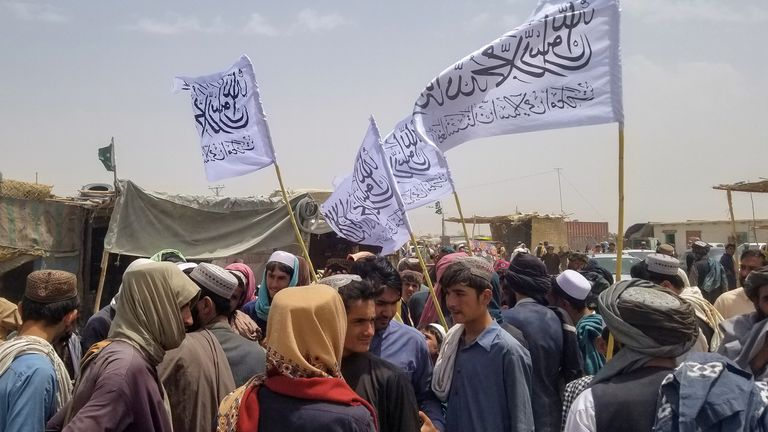 People with Taliban's flags gather to welcome a man (not pictured) who was released from prison in Afghanistan, upon his arrival at the Friendship Gate crossing point at the Pakistan-Afghanistan border town of Chaman, Pakistan August 16, 2021. REUTERS/Saeed Ali Achakzai