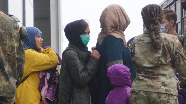 Refugees from Afghanistan board buses at Ramstein air base. The buses will take them to planes that will, in turn, take them to the US