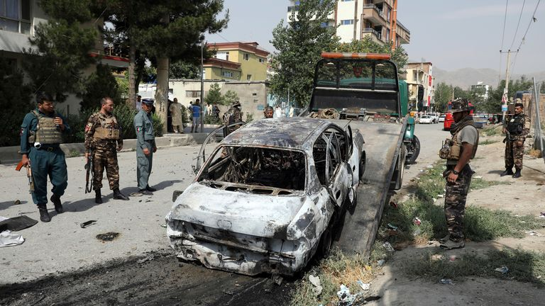 Afghan security personnel inspect a damaged vehicle which was carrying and shooting rockets, in Kabul, Afghanistan, Tuesday, July 20, 2021.