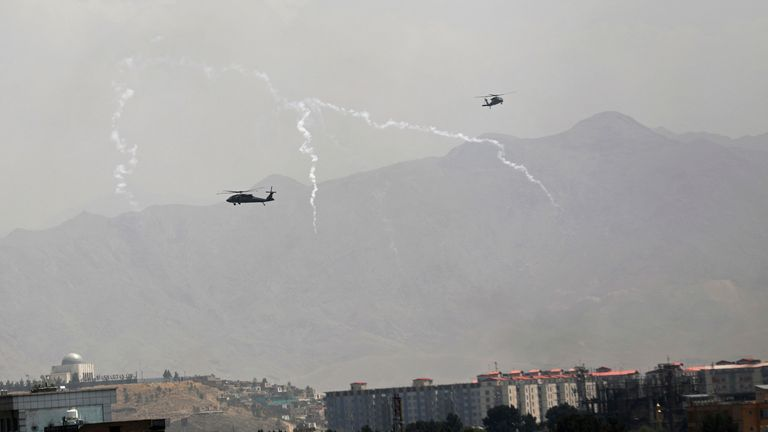 US Black Hawk military helicopters deploy anti-missile decoy flares over the city of Kabul. Pic: AP