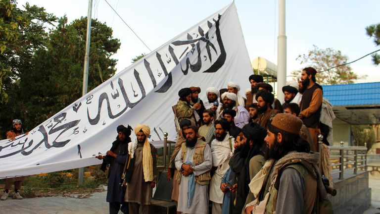 Taliban fighters are pictured in Ghazni, southeastern Afghanistan as they raise their flag. Pic: AP