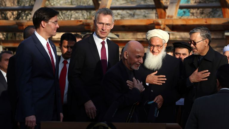 FILE- In this Feb. 29, 2020 file photo, Afghan President Ashraf Ghani, center, arrives with NATO Secretary General Jens Stoltenberg, second left, and then U.S. Secretary of Defense Mark Esper, left, for a joint news conference after the US signed a peace agreement with Taliban militants which includes a May 1, 2021, deadline for a final U.S. troop withdrawal, at the presidential palace in Kabul, Afghanistan. The Biden administration's surprise announcement of an unconditional troop withdrawal fr