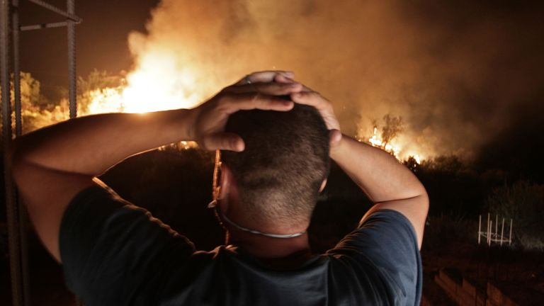 A man looks at a forest fire near the village of Larbaa Nath Irathen, neat Tizi Ouzou, in the mountainous Kabyle region. Pic: AP