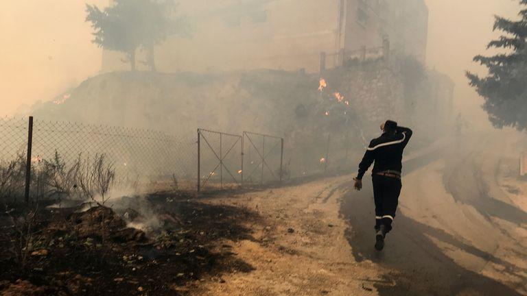 Un soccorritore della protezione civile passa davanti al fumo di un incendio boschivo nella provincia montuosa di Tizi Ouzou, a est di Algeri, Algeria, 10 agosto 2021. REUTERS/Abdulaziz Boumzar