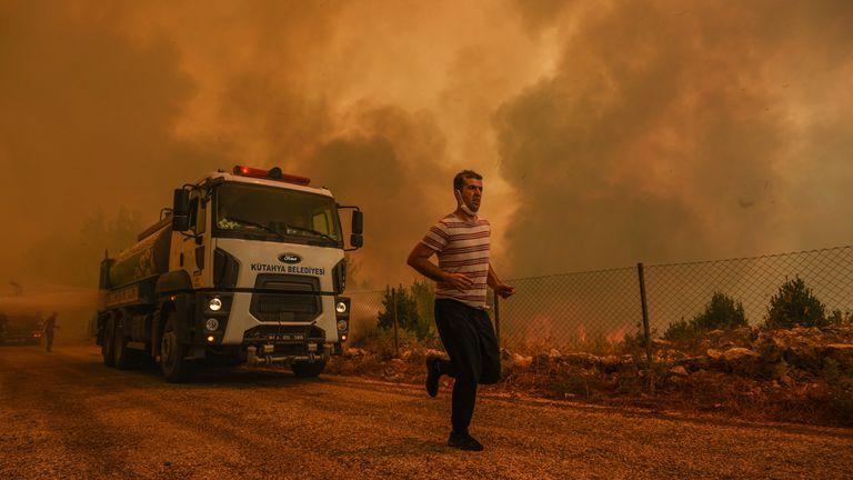 Un uomo corre nel villaggio devastato dal fuoco di Sirtkoy, vicino a Manavgat, Antalya, Turchia, domenica 1 agosto 2021. Pic: AP
