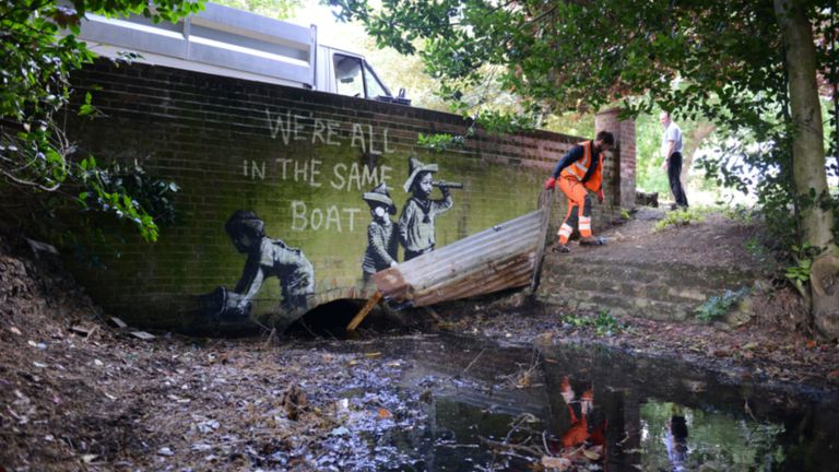 A man in orange overalls removes part of a piece of street art which has appeared on a wall in Nicholas Everitt Park, Lowestoft