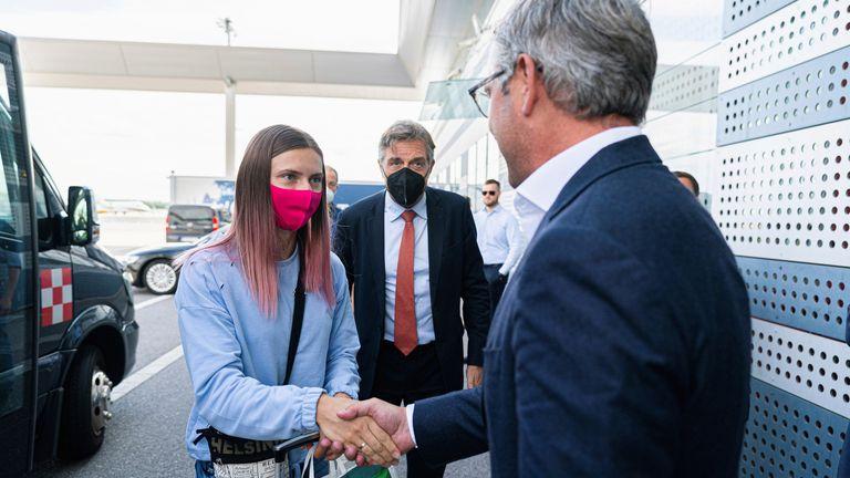Belarusian Sprinter Krystsina Tsimanouskaya shakes hands with Austrian State Secretary Magnus Brunner during a stop at Schwechat airport in Vienna, Austria