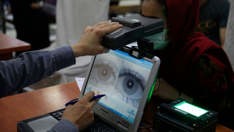 Employee of the passport office scanned eyes of a woman inside the passport office in Kabul, Afghanistan, Wednesday, June 30, 2021. (AP Photo/Rahmat Gul).
