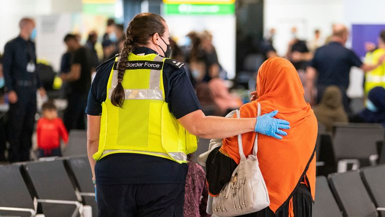 A member of Border Force staff assists a female evacuee as refugees arrive from Afghanistan at Heathrow Airport. Pic: AP