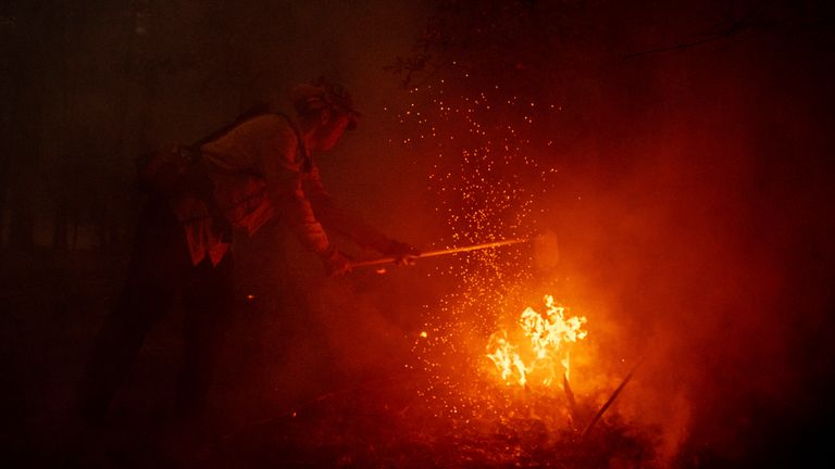 A firefighter battles the Dixie Fire in Genesee, California, 21 August. Pic: AP