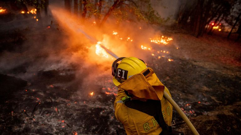 A firefighter hoses down flames from the Dixie Fire in Genesee, California, 21 August. Pic: AP