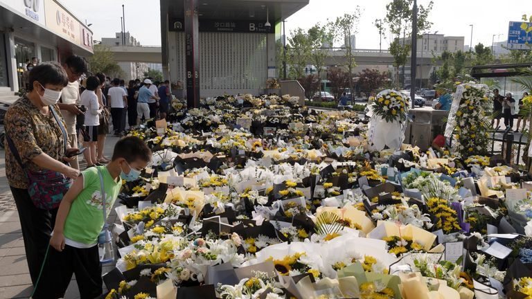 People stand next to flowers placed at an entrance to a subway station of Metro Line 5 in memory of flood victims following heavy rainfall in Zhengzhou, Henan province, China July 27, 2021. Picture taken July 27, 2021. China Daily via REUTERS ATTENTION EDITORS - THIS IMAGE WAS PROVIDED BY A THIRD PARTY. CHINA OUT.