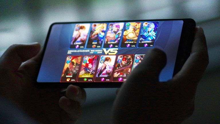 """--FILE--A Chinese mobile game player plays Tencent's mobile MOBA """"King of Glory"""" or """"Honor of Kings"""" on his smartphone in Ji'nan city, east China's Shandong province, 9 September 2018. ..Enthusiasm for new game titles and the development of industrial software are the key factors that will determine the future financial health of tech giant Tencent Holdings Ltd following the release of the company's second quarter earnings. Tencent came out of an extended regulatory freeze in new games as it rode Peacekeeper Elite and other titles like Honor of Kings to reignite growth in a business that contributed 30 percent of its revenue. The company said it released 10 games in the second quarter."""