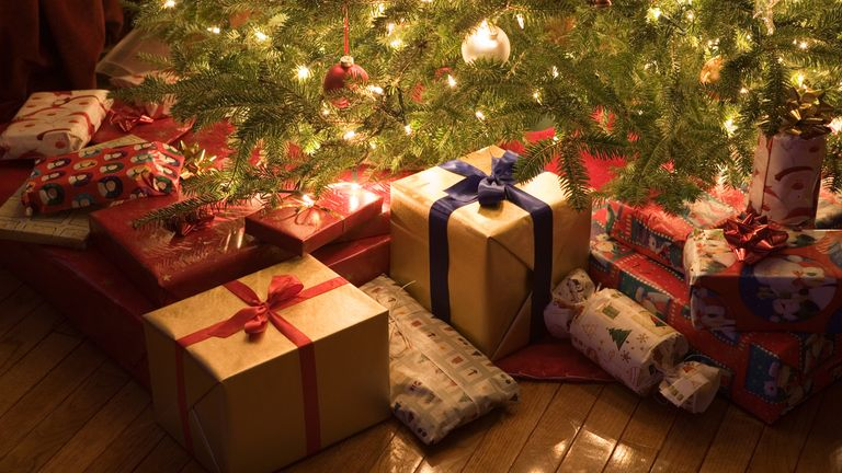 colorful wrapped gifts under brightly lit Christmas tree