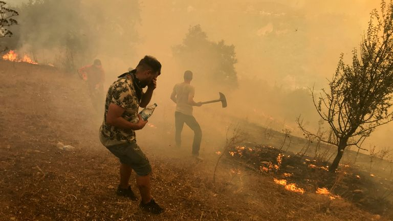 Villagers attempt to put out the flames of a wildfire in the mountainous Kabylie region of Tizi Ouzou, east of Algiers, Algeria