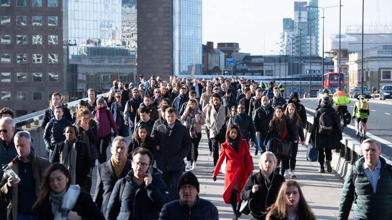 Commuters crossing London Bridge, in central London, during the morning rush hour prior to lockdown