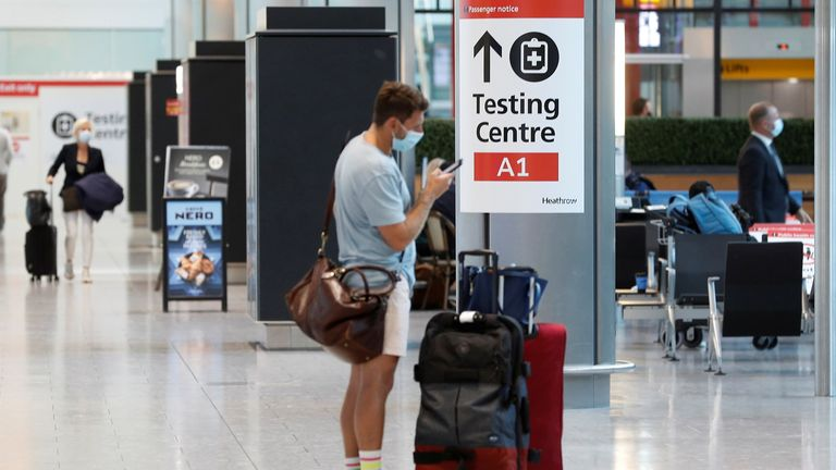 A passenger stands next to a COVID-19 testing centre sign at Heathrow Airport