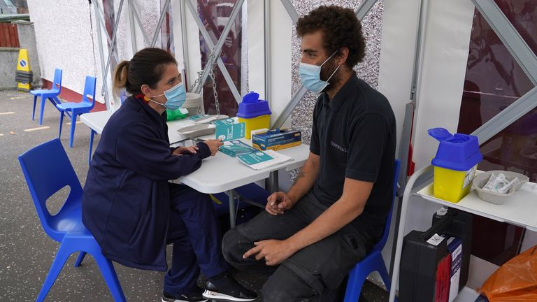 Vaccinator Suzanne Pozzo gives a vaccine to Omar Khalifa in a pop up tent at a drop in clinic outside Stenhousemuir Football Ground after Scotland moved to Level 0 of the country's five-tier coronavirus restrictions system. Picture date: Tuesday August 3, 2021.