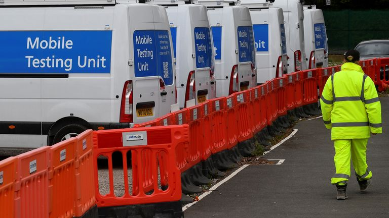 A worker walks past coronavirus disease (COVID-19) mobile testing vehicles parked at a depot in London