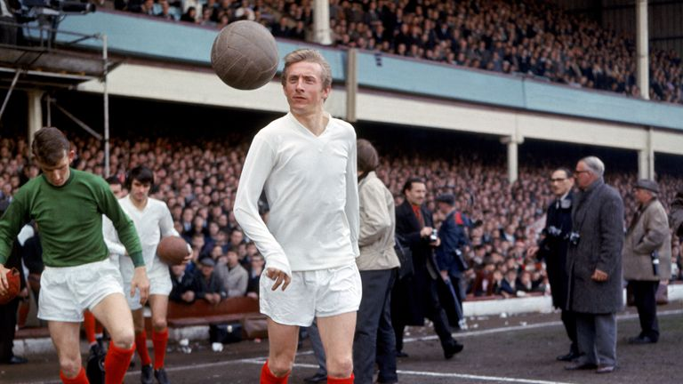 Denis Law keeps his eyes on the ball as he walks out onto the pitch followed by teammates Alex Stepney and George Best