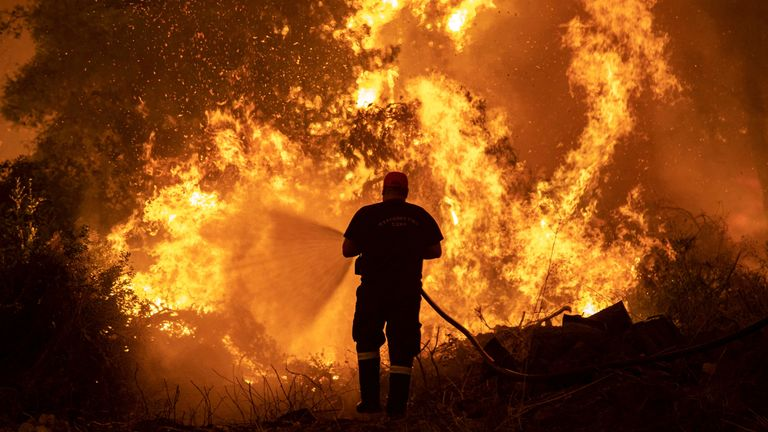 A firefighter tries to extinguish a wildfire burning in the village of Pefki, on the island of Evia, Greece, August 8, 2021. REUTERS/Nikolas Economou