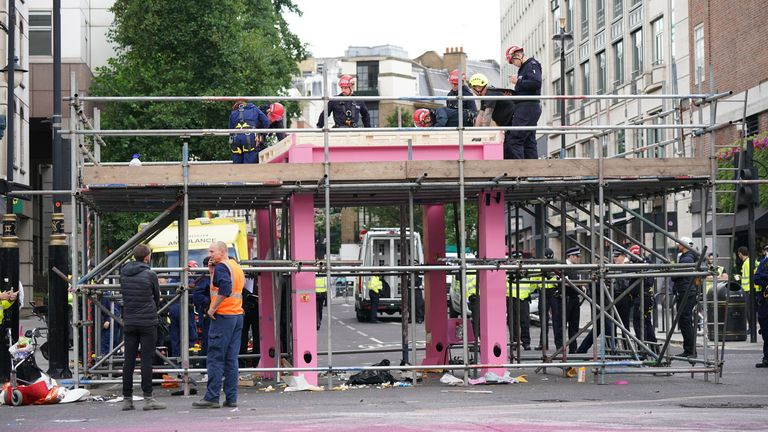 Workers remove a large pink structure blocking the junction of Long Acre and Upper St Martin's Lane in London which was constructed on Monday by environmental activists from Extinction Rebellion.