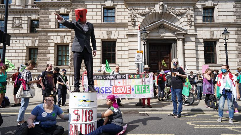 Extinction Rebellion protests A man wearing a petrol can as a face mask speaks from the top of a barrel as climate activists from Extinction Rebellion hold a protest outside the offices of HM Revenue and Customs (HMRC) in Whitehall, Westminster, central London. Picture date: Tuesday August 24, 2021.