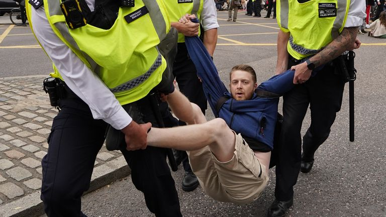 Police remove a man as members of Extinction Rebellion reach Tower Hill during their march in central London