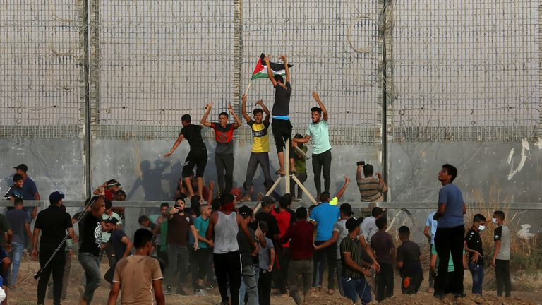 Protestors tried to climb the border fence during the demonstration. Pic AP