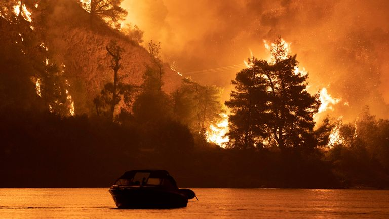 Wildfires continue in Evia Flames rise as a wildfire burns in the village of Limni, on the island of Evia, Greece, August 6, 2021. Picture taken August 6, 2021. REUTERS/Nicolas Economou