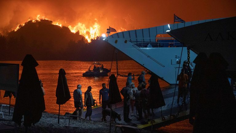 People board a ferry during evacuation as a wildfire burns in the village of Limni, on the island of Evia, Greece, August 6, 2021. Picture taken August 6, 2021. REUTERS/Nicolas Economou