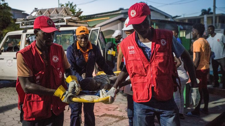 Red Cross paramedics carry an injured girl in Les Cayes, Haiti, on 14 August