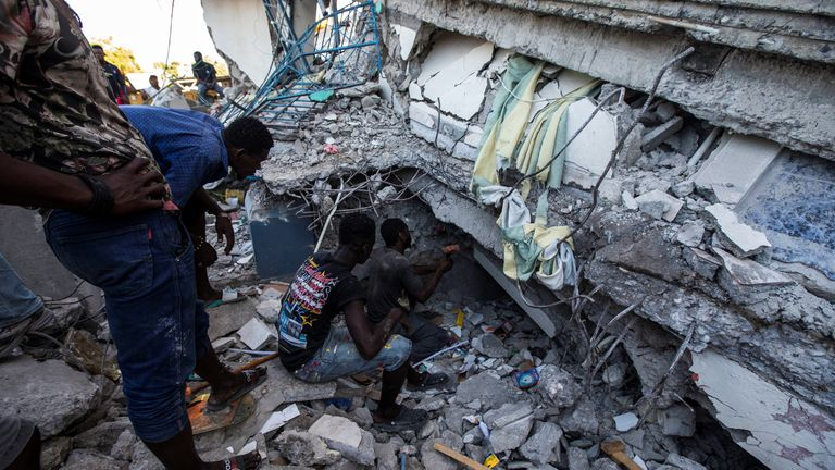 People look for survivors in a house destroyed following the 7.2-magnitude earthquake in Les Cayes, Haiti, on 14 August