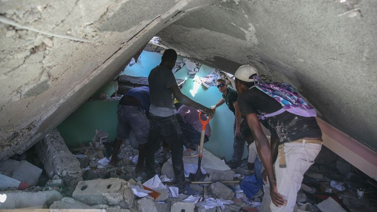 Rescue workers search for survivors in a destroyed home in Les Cayes