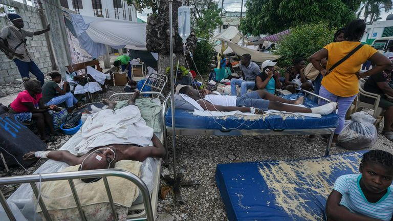 Injured people lie in beds outside the Immaculée Conception hospital in Les Cayes. Pic: AP