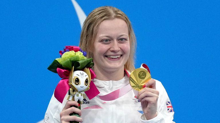 Hannah Russell pose avec sa médaille d'or sur le podium après avoir remporté le 100 mètres dos féminin