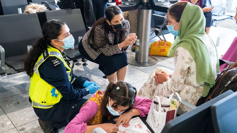 Home Secretary Priti Patel talking to a refugee from Afghanistan who arrived on a evacuation flight at Heathrow Pic: AP