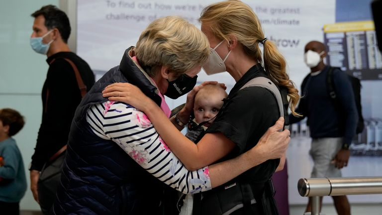 A grandmother meets her grandchild for the first time after EU and US travellers were allowed into the UK without the need to isolate
