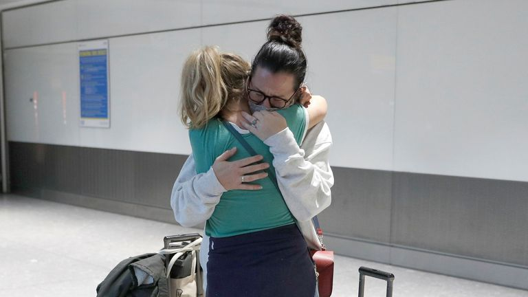 Women embrace at the International arrivals area of Terminal 5 in London's Heathrow Airport, Britain, August 2, 2021. REUTERS/Peter Nicholls