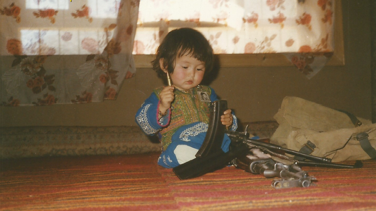 Homira plays with an AK47 as a toddler growing up in Afghanistan