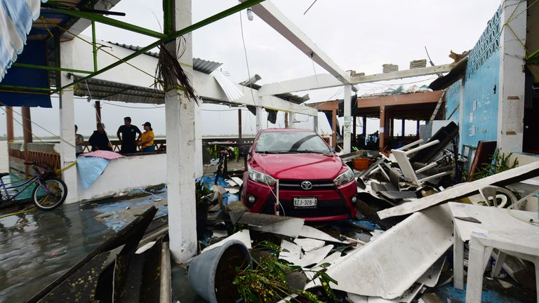 A car stands parked amidst the debris of restaurants that were destroyed after Hurricane Grace slammed into the coast with torrential rains, in Costa Esmeralda, near Tecolutla, Mexico August 21, 2021. REUTERS/Oscar Martinez